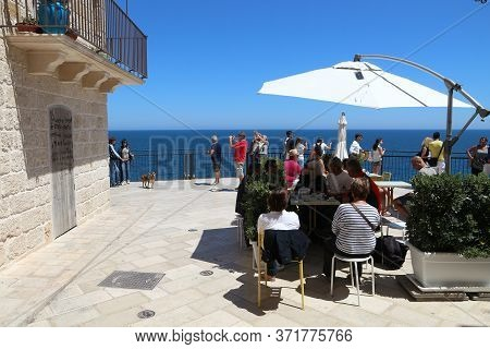 Polignano A Mare, Italy - May 29, 2017: People Sit In A Cafe In Polignano A Mare Old Town In Apulia,