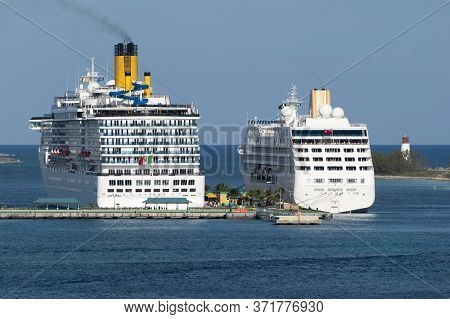 The View Of Two Large Moored Cruise Liners And Paradise Island Lighthouse In A Background (nassau, B