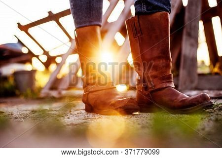 The Girl Stands On The Ranch In Cowboy Boots And Catches The Rays Of The Setting Sun.