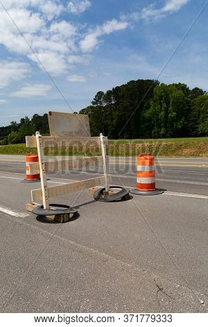 Rear View Of Traffic Barricade And Safety Barrels, Asphalt Roadway Copy Space, Blue Sky And Trees, V