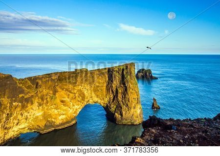 Cape Dyrholaey. Travel to the fabulous island of Iceland. The southern edge of Iceland. Giant rock ledge - arch. Volcanic cliffs above a black sand beach