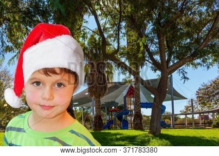 Handsome boy in Santa Claus hat smiling. Children 's playground with a multicolored attractions. The concept of physical and mental development of children