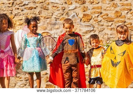 Row Of Children In Halloween Costumes Hold Hands Over Stone Wall