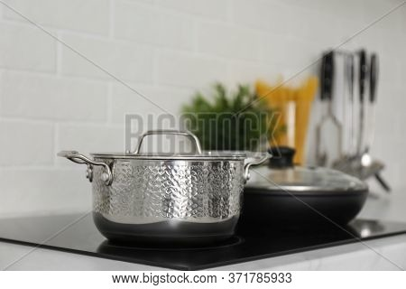 Saucepot And Frying Pan On Induction Stove In Kitchen