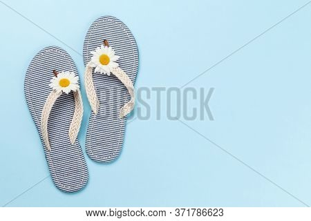 Sea flip flops with camomile decor on blue background. Summer vacation concept. Flat lay with copy space