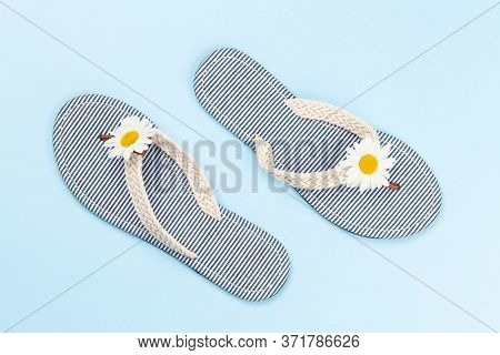 Sea flip flops with camomile decor on blue background. Summer vacation concept. Flat lay