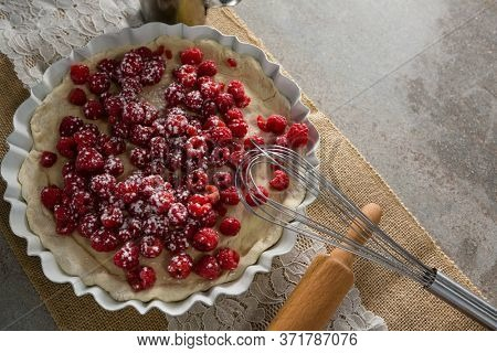 Close-up of red berries on tart with whisker and rolling pin