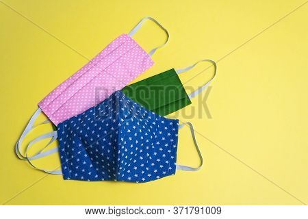 Three Colored Different Reusable Medical Masks On Yellow Isolated Background. Hygienic, Antimicrobia