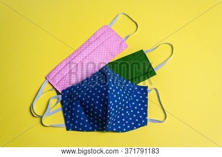 Three Colored Different Reusable Medical Masks On A Yellow Isolated Background. Hygienic, Antimicrob