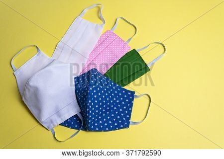 Five Colored Different Reusable Medical Masks On Yellow Isolated Background. Hygienic, Antimicrobial