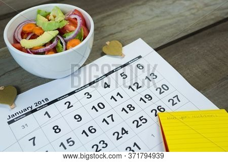 Calendar with new year resolution and diet food on wooden table