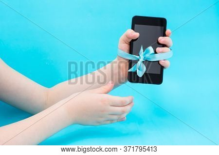 Digital Detox Concept. A Children's Hand With A Smartphone Is Tied With A Blue Ribbon And A Second H
