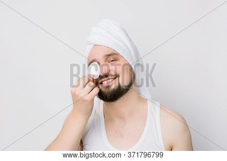 Smiling Handsome Guy With A White Towel On His Head Cleaning Face Skin With Cotton Pad. Attractive M