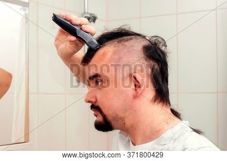Portrait Of Adult Man With Serious Face And Hair Clipper Shaving Head In Bathroom, Long Hair Falling