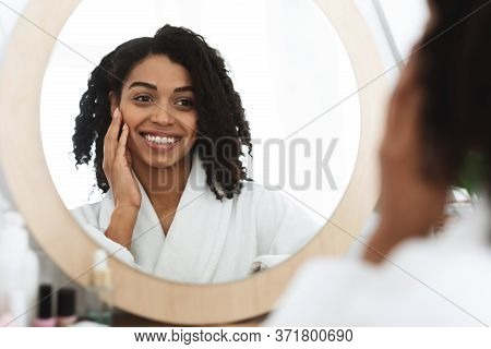 Skin Detox. Happy African American Woman Touching Her Beautiful Face While Looking In The Mirror In