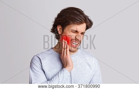 Endure Pain. Sad Man Suffers From Pain In His Teeth And Presses Hand To Red Spot, Isolated On Gray B