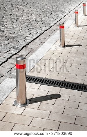 Restrictive Columns On An Old Cobblestone Road. Street Paving. Cobblestone Pavement. Background For
