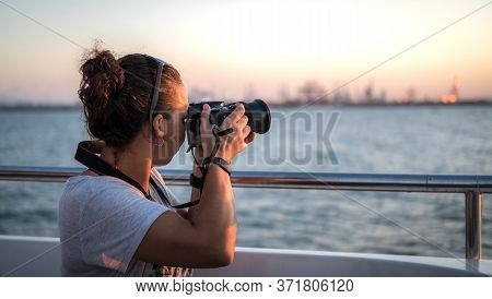 Woman Traveler On A Ship Watching The Sunset Seascape, With Bridge Camera Photo For Travel