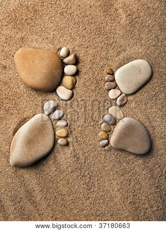 trace bare feet made ??of pebble stones on the beach sand background