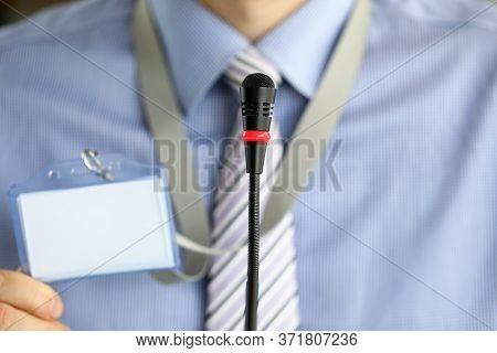 Close-up Of Modern Microphone. Male Person Holding Badge With Personal Information. Businessman On M
