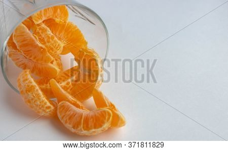 Tangerine Slices In A Glass Glass On A Light White Background. Tangerines Close-up. Fruit. Fruits Wi