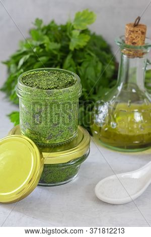 Pesto In Glass Jar With Mockup Lug Lid, Green Leaves Of Herbs, Basil, Parsly And Olive Oil And Salt