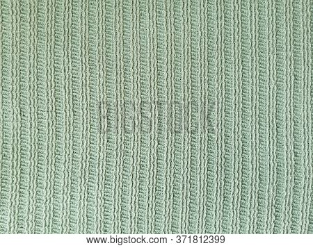 Knitted Textile Texture With A Vertical Pale Green Hue. Knitted Texture Pattern. Texture Of Knitted