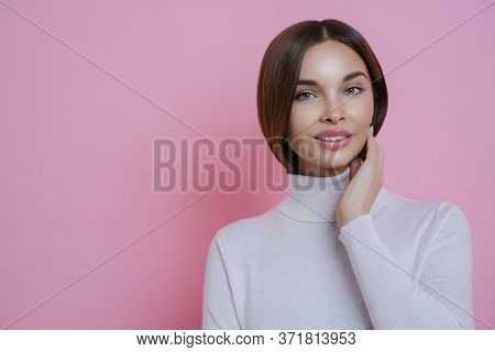 Natural Looking Young European Female Model Smiles Gently At Camera, Has Well Cared Dark Hair, Dress
