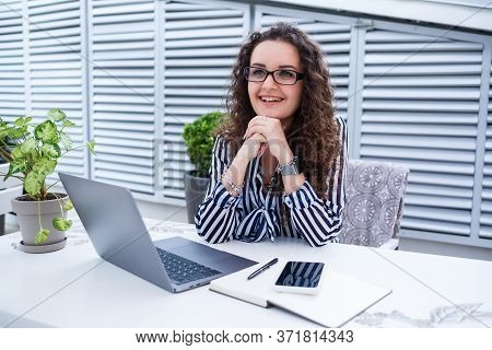 Beautiful Young Woman Working On A Laptop And Smiling While Sitting Outdoors In A Cafe. Young Woman