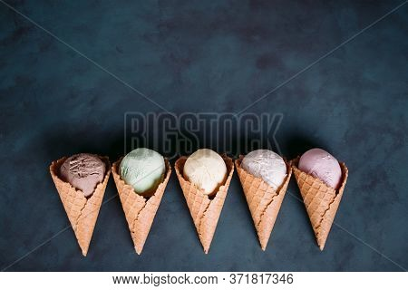 Ice Cream Background. Various Flavored Ice Dessert Scoops In Waffle Cones On Dark Table. Food, Summe