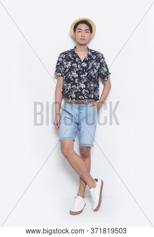 full length Summer man wearing new stylish floral, plant ,leaves fern printed short shirts with hat , blue jeans shorts and white and white sneaker, shoes