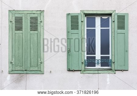 A Window With Open Wooden Shutters And Window With Closed Shutters On A Plastered Wall