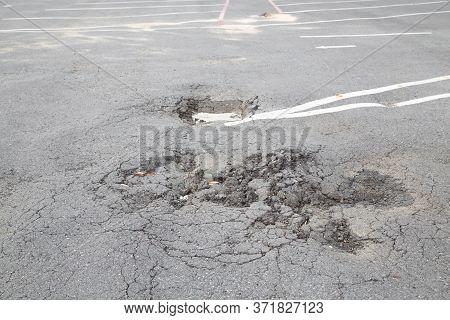 Damaged Road. Deep Crack On The Asphalt.water Filled Pot Hole In The Road