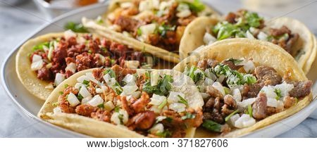 platter of mexican street tacos with carne asada, chorizo, and al pastor in corn tortillas