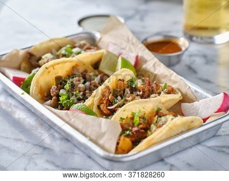 tray of mexican street tacos with carne asada, chorizo, and al pastor in corn tortillas