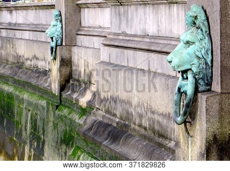 Covered In Green Patina Lion Heads With Rings In Their Teeth On The Waterfront Thames In London