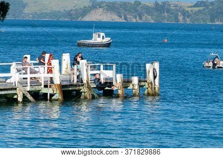 Kawau Island, New Zealand - December 26 2014: Young Man Taking A Leap From Pier Into Blue Water.