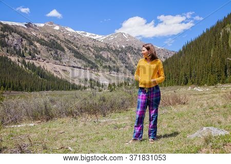 Beautiful Young Brunette Woman Enjoys Beautiful Mountain Landscape While Traveling.