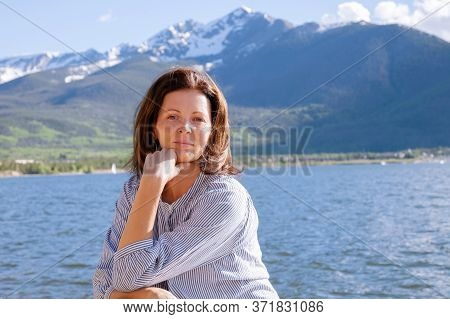 Portrait Of A Beautiful Young Woman Resting On The Shore Of A Mountain Lake On A Sunny Day. Pretty G