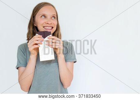 Fascinated Young Woman Holding Chocolate Bar In Gold Foil, Smiling, Enjoying, And Looking Away. Port