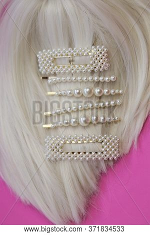 Pearl Hair Clips On Blond Hair . Fashionable Hair Accessories. Hairpin With Pearls On A Bright Pink