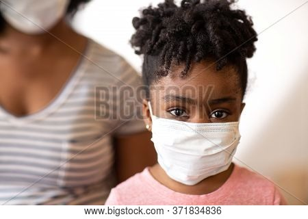 African American Mother Helping Her Daughter Put On A Face Mask.