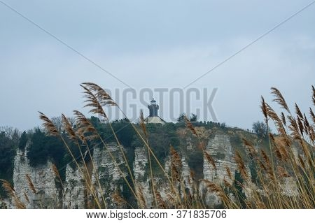 Lighthouse On A Chalk Cliff Under A Grey Sky In Normandy, France