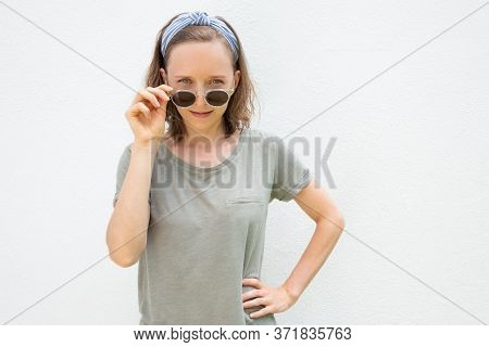 Cheerful Young Woman Wearing Hairband And Summer Clothes, Taking Off Sunglasses, Looking At Camera O