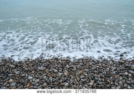 French Coastline Of Normandy In France With Pebbles Beaches, Part Of The Typical Landscape