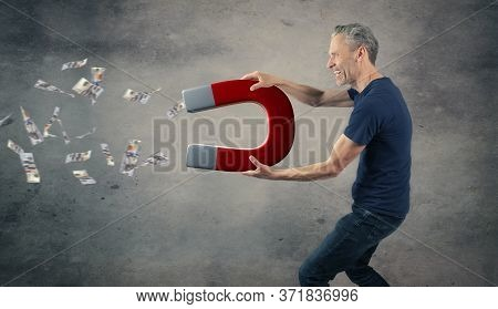 Happy Man With A Big Magnet Attracting Money, Abundance Or Wealth Concept