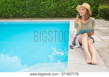 Thoughtful Inspired Woman With Tablet And Stylus Sitting At Swimming Pool, Thinking Over Ideas. Outd