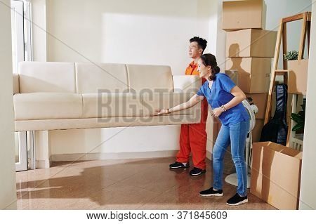 Mature Asian Woman Telling Moving Men Where To Put Sofa They Are Carrying, Horizontal Shot, Copy Spa