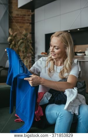 Housewife Looking At Pullover While Sitting With Laundry On Laps