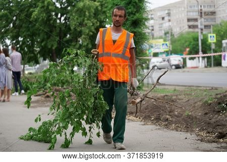 June 11, 2020, Russia, Magnitogorsk. A Utility Worker Recycles Dry Branches From Trees On A City Str